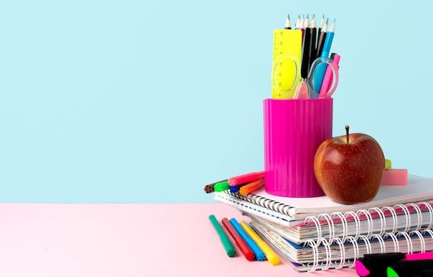 Vista frontal do material escolar de volta com cadernos e espaço de cópia