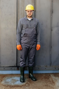 Vista frontal do mecânico masculino com óculos de proteção e capacete