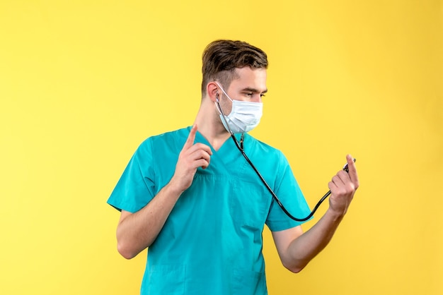 Vista frontal do médico com estetoscópio e máscara na parede amarela