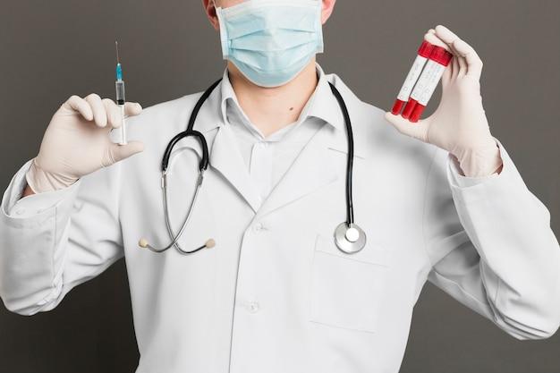 Vista frontal do médico com estetoscópio segurando a seringa e vacutainers