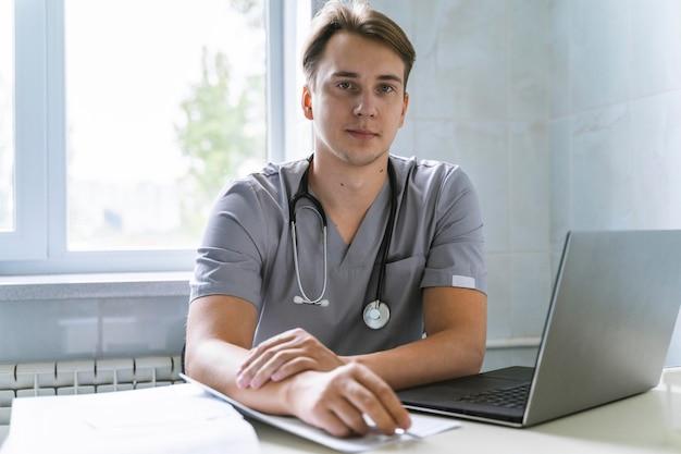 Vista frontal do médico com estetoscópio trabalhando no laptop