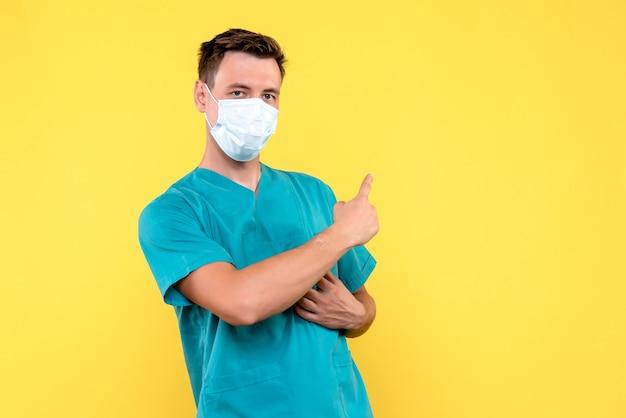 Vista frontal do médico com máscara estéril no piso amarelo emoção médico hospital masculino
