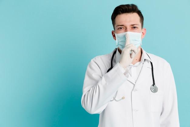 Vista frontal do médico com máscara médica e luvas cirúrgicas, fazendo o sinal silencioso