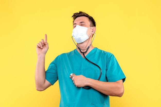 Vista frontal do médico com tonômetro e máscara na parede amarela