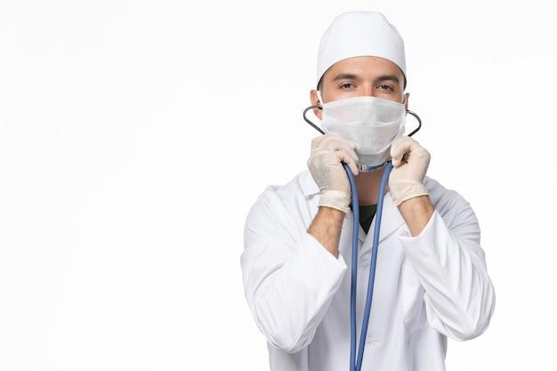 Vista frontal do médico do sexo masculino em traje médico e máscara devido a covid - usando um estetoscópio na parede branca covid - doença por vírus pandêmico