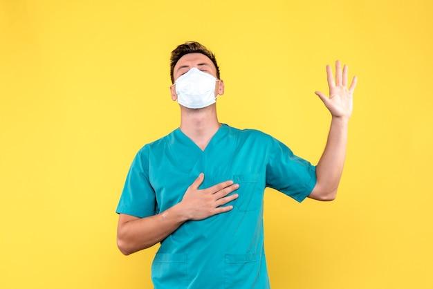 Vista frontal do médico em pose de palavrão na parede amarela