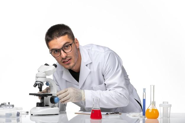 Vista frontal do médico em terno branco trabalhando com soluções no espaço em branco