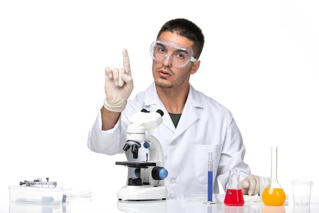 Vista frontal do médico em terno médico branco sentado com soluções no espaço em branco