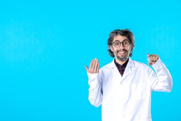 Vista frontal do médico em uniforme médico segurando o pequeno frasco no azul