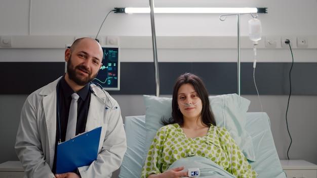 Vista frontal do médico especialista e mulher doente, tendo uma conferência de videochamada online com o médico durante a consulta de doença na enfermaria do hospital. paciente discutindo recuperação de doença
