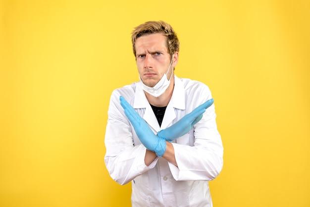 Vista frontal do médico masculino com máscara em covidemia pandêmica de fundo amarelo