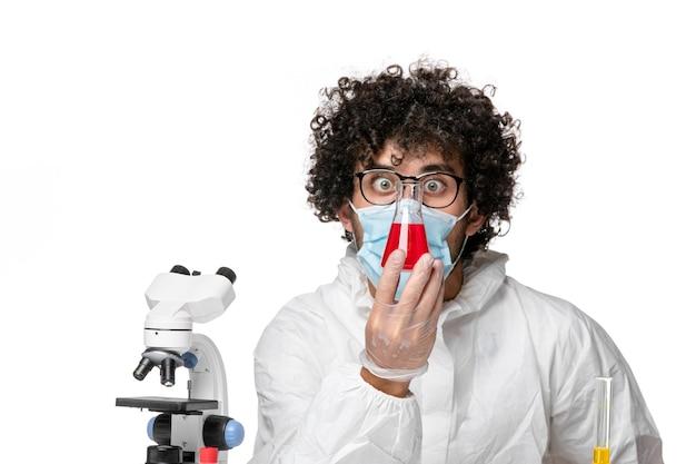 Vista frontal do médico masculino com traje de proteção e máscara segurando o frasco com solução vermelha sobre fundo branco.