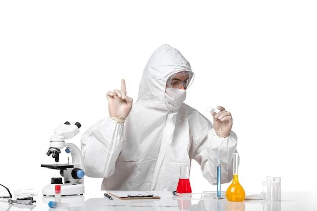 Vista frontal do médico masculino em traje de proteção com máscara devido a cobiçoso trabalhando no espaço em branco