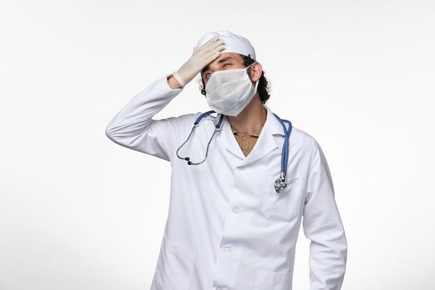 Vista frontal do médico masculino em traje médico e usando uma máscara como proteção contra covid - tendo dor de cabeça no vírus da doença da parede branca covidemia