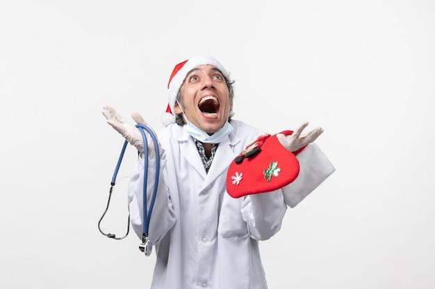 Vista frontal do médico regozijando-se com o vírus da parede branca, saúde cobiçosa do feriado