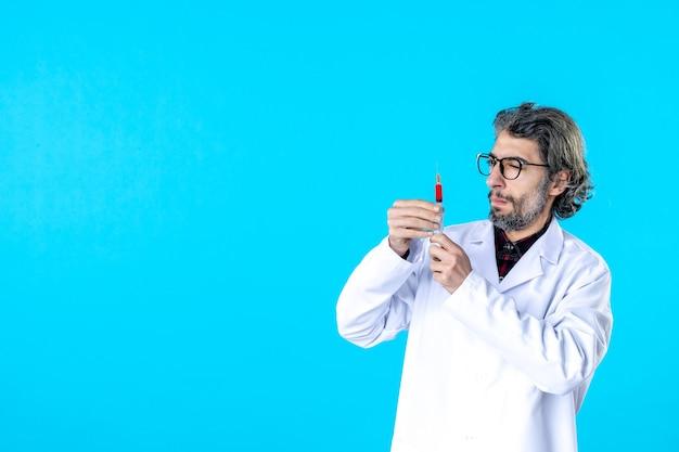 Vista frontal do médico segurando a injeção em azul