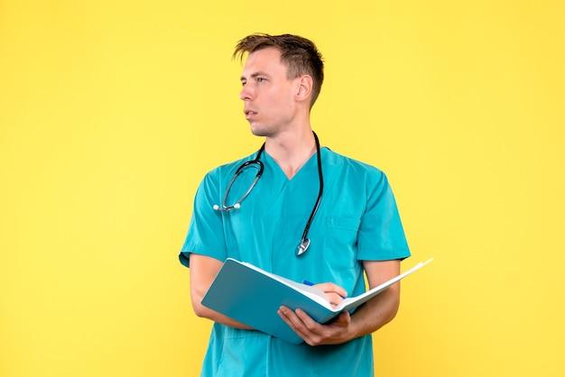Vista frontal do médico segurando análises em arquivos na parede amarela