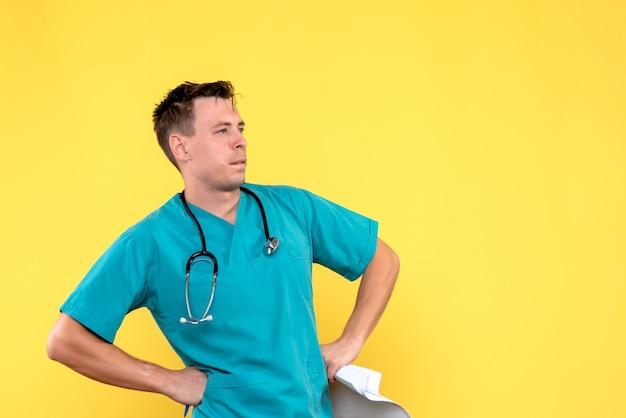 Vista frontal do médico segurando análises na parede amarela clara