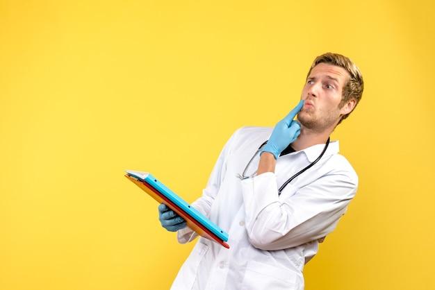 Vista frontal do médico segurando análises sobre o fundo amarelo médico vírus saúde humana