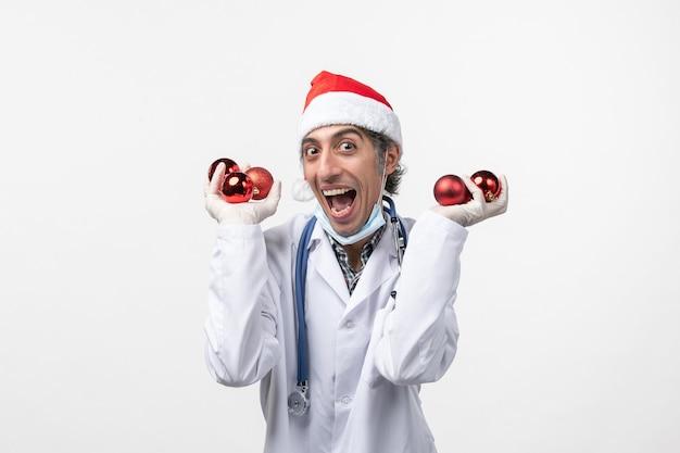 Vista frontal do médico segurando brinquedos na parede branca covid- emoção vírus da saúde