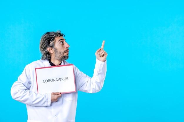 Vista frontal do médico segurando coronavírus escrito em azul