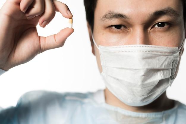 Vista frontal do médico segurando um comprimido