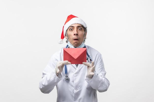 Vista frontal do médico segurando um envelope vermelho sobre o vírus da saúde de parede branca