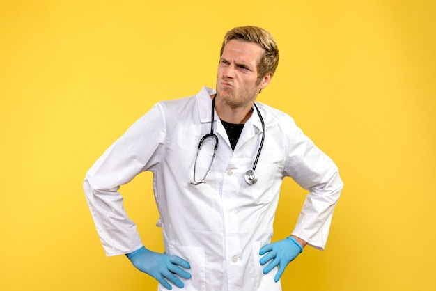 Vista frontal do médico sobre fundo amarelo saúde médico vírus humanos