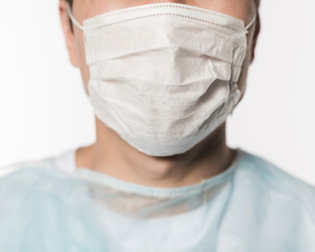 Vista frontal do médico usando máscara médica