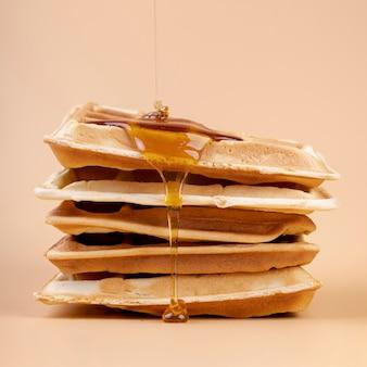 Vista frontal do mel pingando em waffles