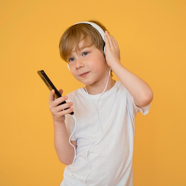 Vista frontal do menino bonitinho ouvindo música