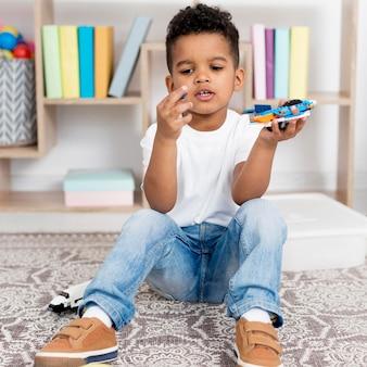 Vista frontal do menino brincando com brinquedo