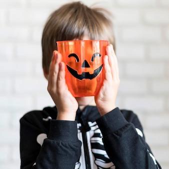 Vista frontal do menino com conceito de abóbora