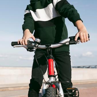 Vista frontal do menino com sua bicicleta do lado de fora