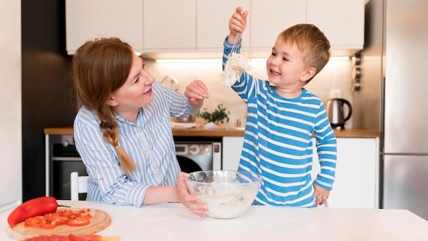 Vista frontal do menino cozinhando em casa