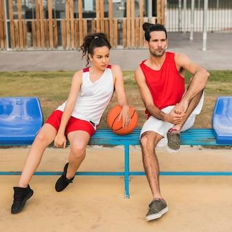 Vista frontal do menino e menina com bola de basquete