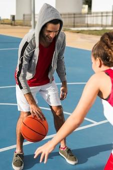 Vista frontal do menino e menina jogando basquete