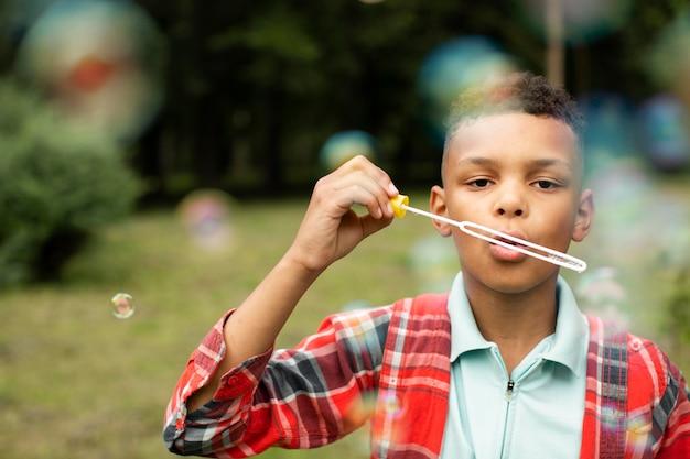 Vista frontal do menino fazendo bolhas de sabão