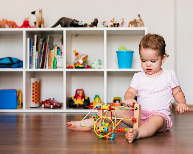 Vista frontal do menino feliz e fofo brincando com brinquedos