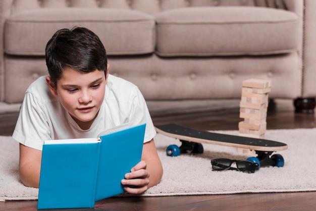 Vista frontal do menino lendo um livro