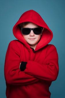 Vista frontal do menino moderno com óculos de sol posando