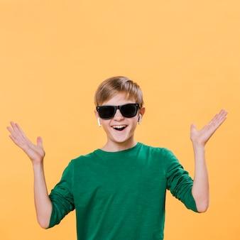 Vista frontal do menino moderno com óculos de sol