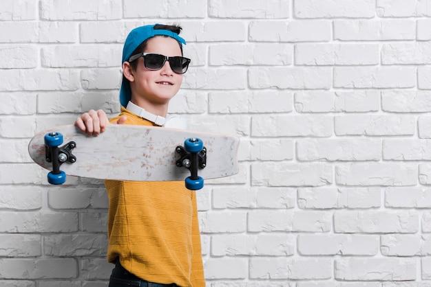Vista frontal do menino moderno com skate