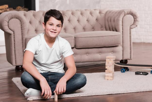 Vista frontal do menino moderno, sentada no chão