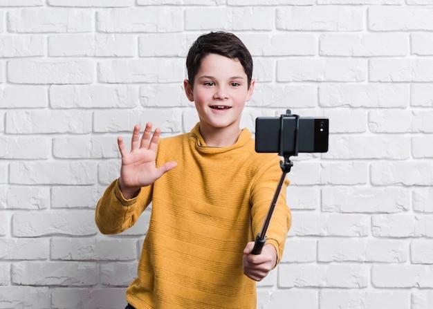 Vista frontal do menino moderno tomando uma selfie