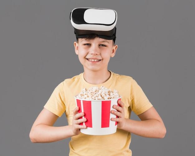 Vista frontal do menino sorridente com fone de ouvido de realidade virtual segurando pipoca