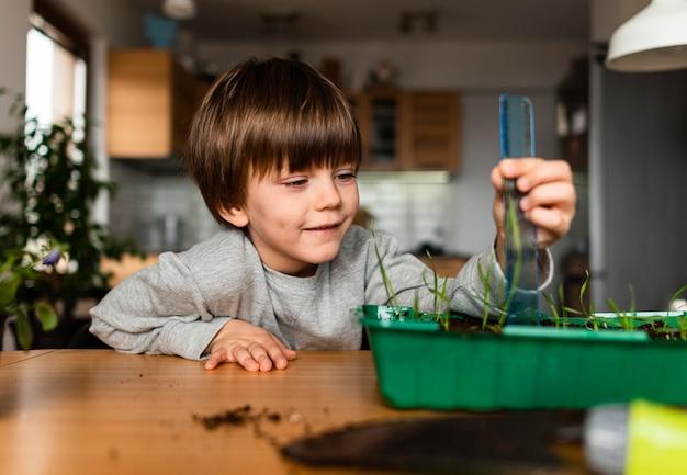 Vista frontal do menino sorridente, medindo planta crescendo em casa
