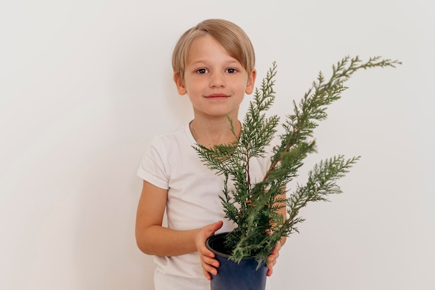 Vista frontal do menino sorridente segurando o vaso de planta