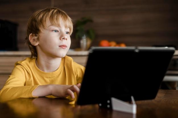 Vista frontal do menino usando o tablet em casa