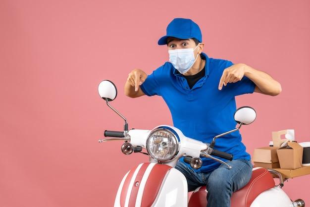 Vista frontal do mensageiro com máscara médica usando chapéu, sentado na scooter e apontando para baixo sobre um fundo de pêssego pastel